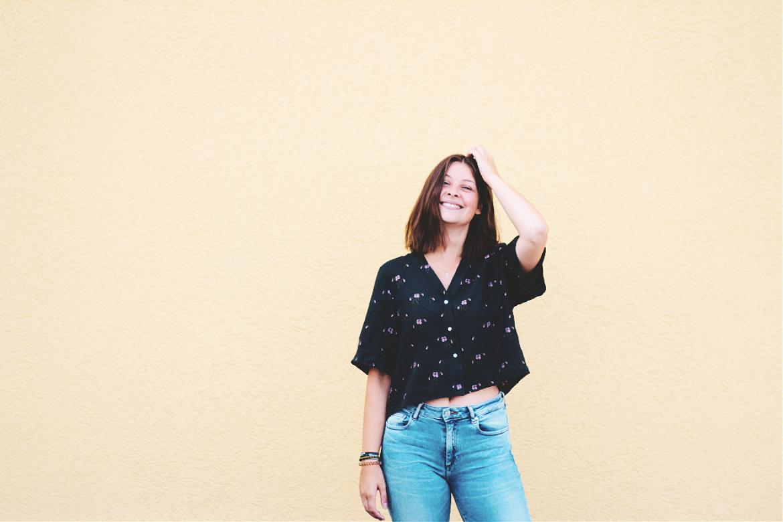Frau lächelt vor gelber Wand