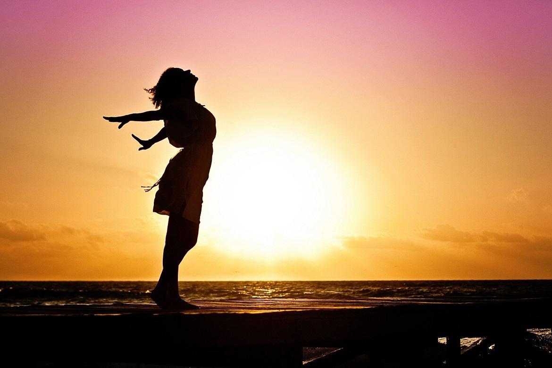 Atmung; Frau vor einem Sonnenuntergang