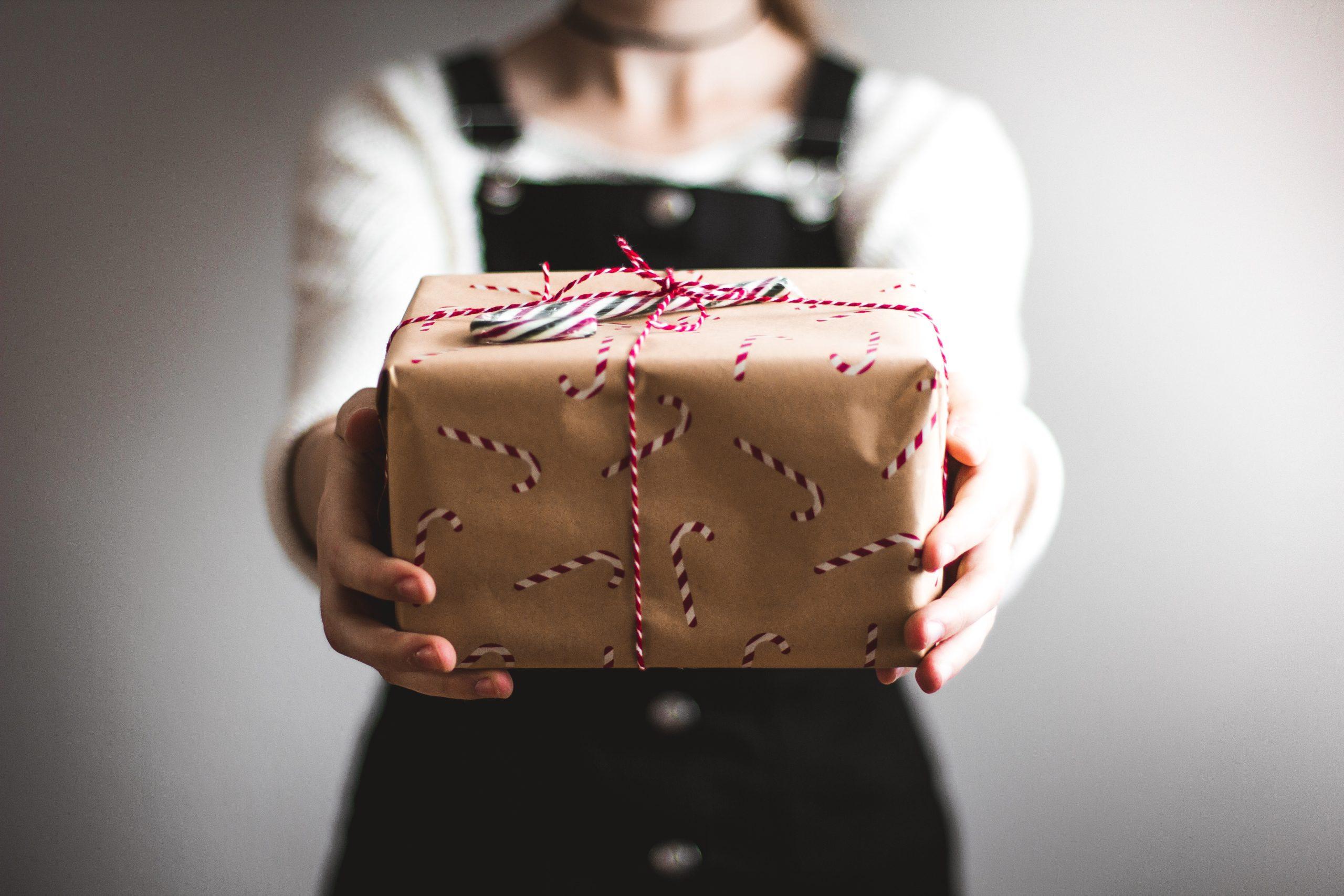 Frau reicht Weihnachtsgeschenk